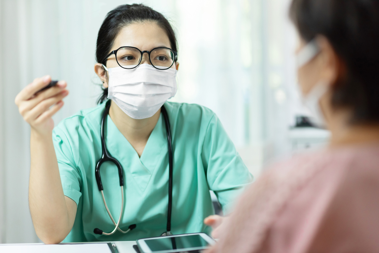 Photo of of a doctor in a mask with patient. Doctor is empathetic to patient.