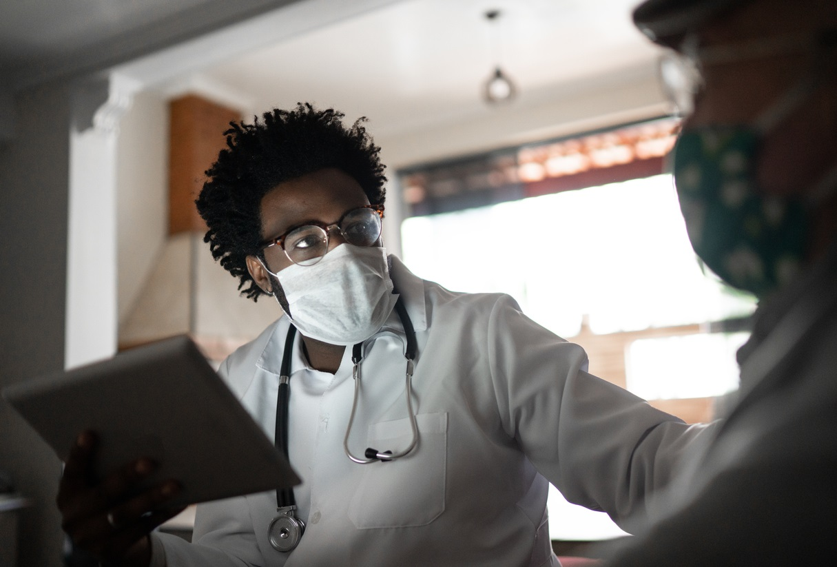 photo of a doctor wearing a facemask and working hard