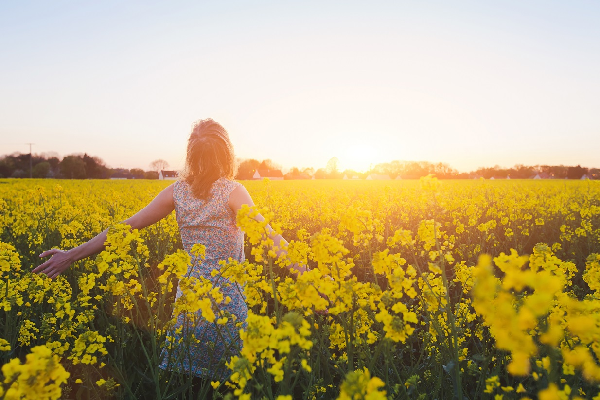 photo of a happy young woman enjoying summer in yellow field at sunset, conveys mindfulness and empathy