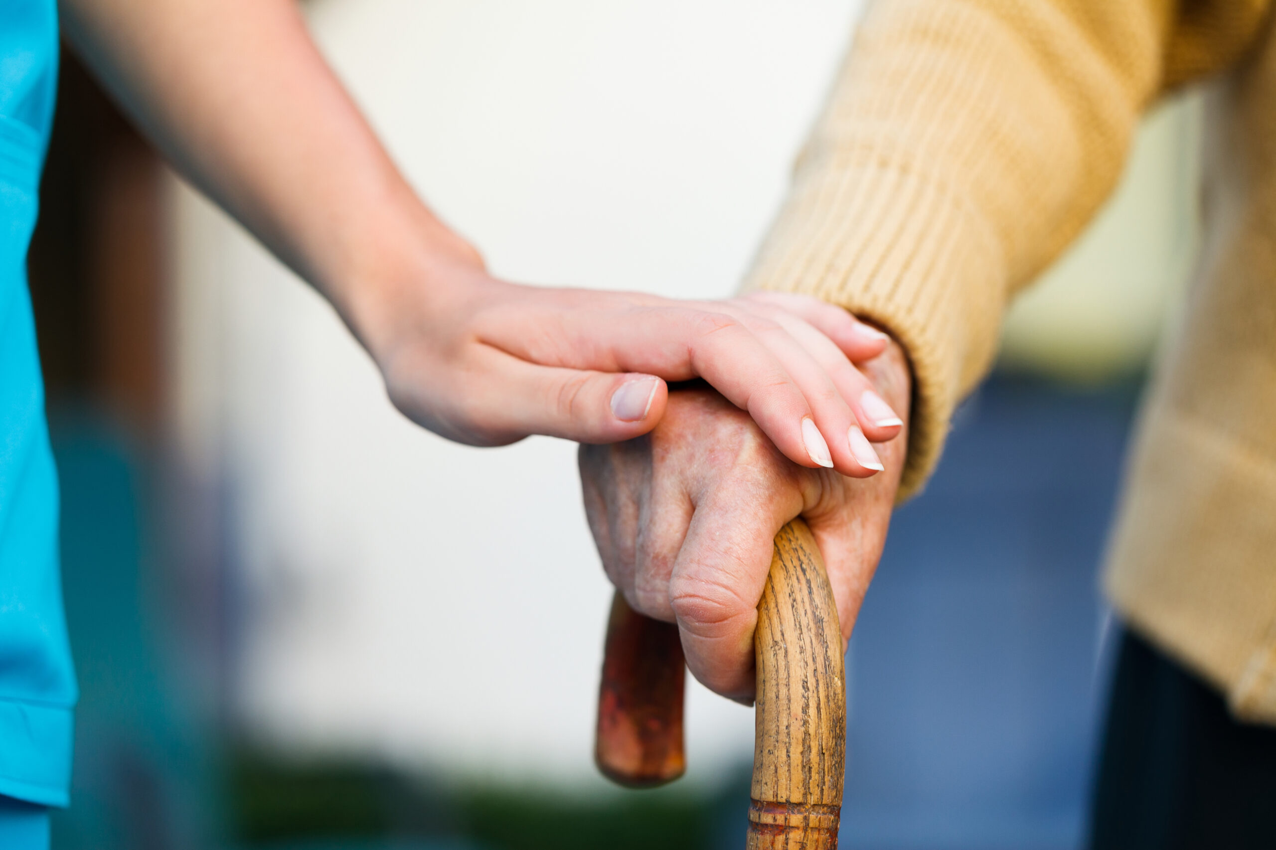Photo of a doctor holding a senior patient hand.
